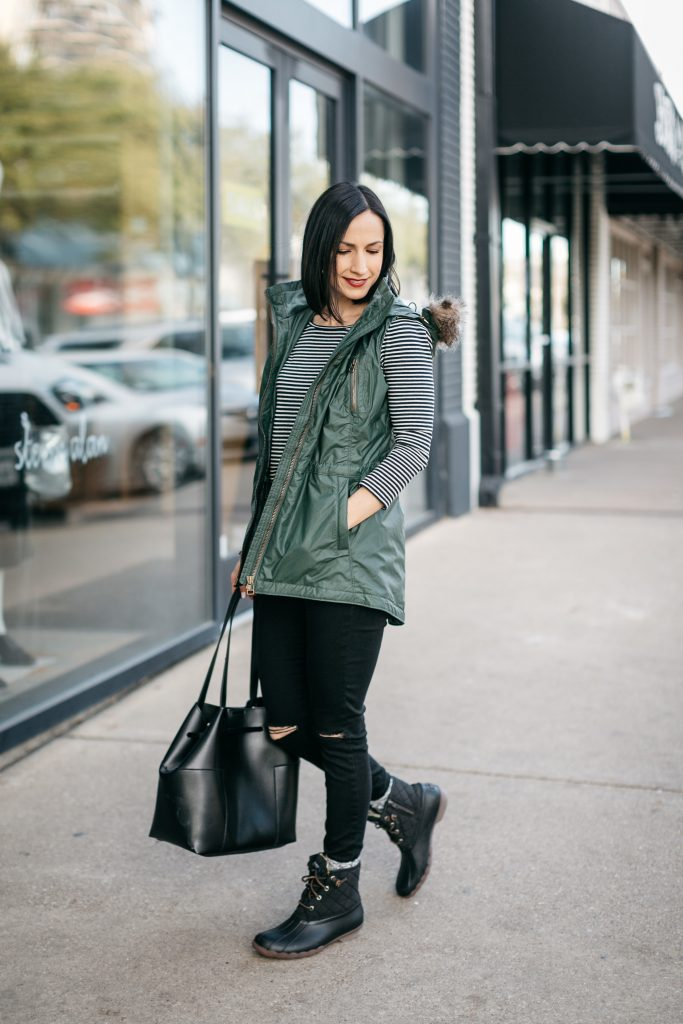 How to style Sperry Duck boots. Create an outfit around your boots with a striped tee, black ripped jeans, and a vest. Athleta makes great down vests that are functional and fashionable.